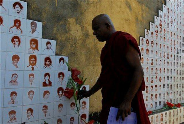 A Sri Lanka Buddhist monk places flowers at a monument during a commemoration of disappeared people at Raddoluwa, a suburb of Colombo, Sri Lanka. Photo: Eranga Jayawardena
