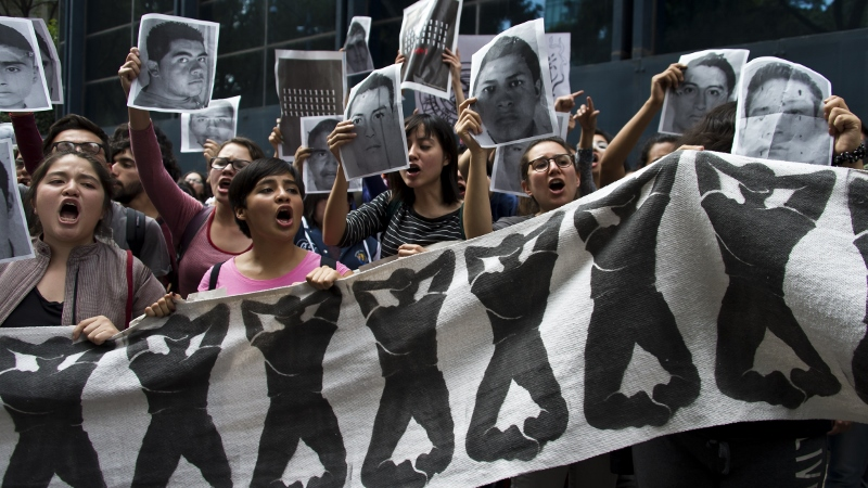 Students chant slogans in front of the Attorney General's Office in Mexico City during a protest over then 43 students missing in Iguala, Guerrero State. Photo: AFP