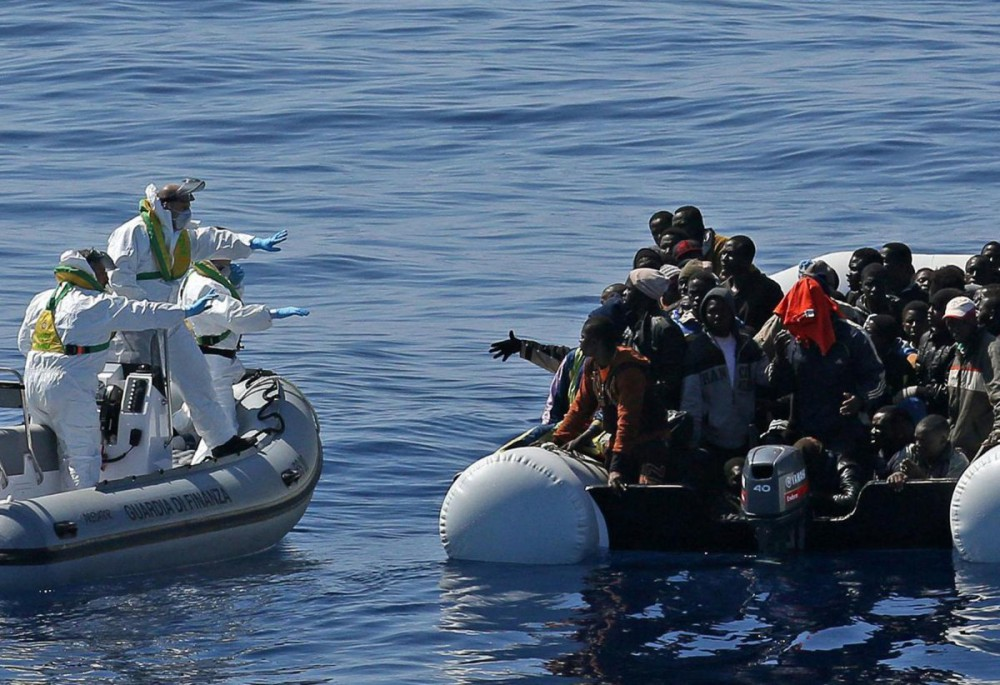 An Italian Financial Police rescue unit approaches an inflatable dinghy crowded with migrants off the Libyan coast. Photo_ www.businessinsider.com