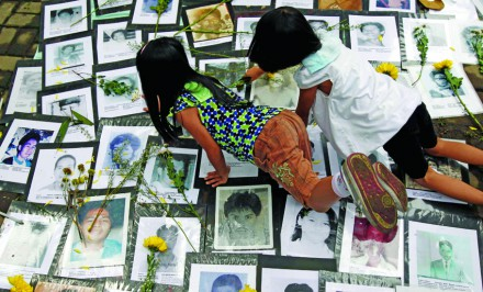 Children place flowers on pictures of disappeared victims in front of a memorial shrine in Manila