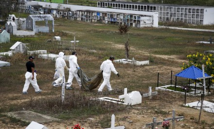 Forensic science workers carry an unidentified body at the cemetery in La Macarena, Colombia. Investigators are digging up bodies in hopes of identifying 464 people buried in unmarked graves. Photo credit: AP/Fernando Vergara